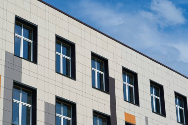 facade of a modern building on a bright Sunny day, siding and Windows, beautiful exterior of the new building
