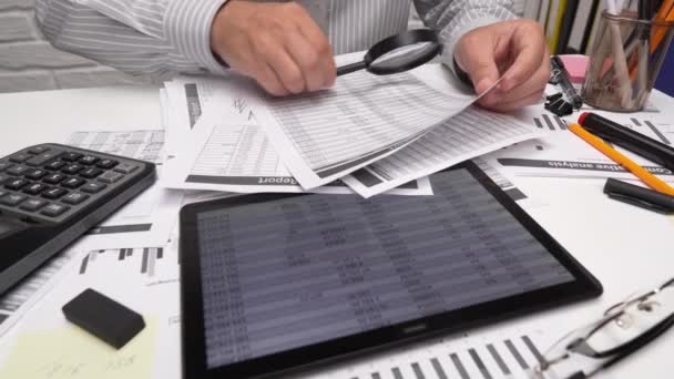 Business analysis and accounting concept - businessman working with document, spreadsheet, using calculator, tablet pc. Office desk closeup.
