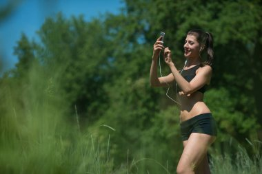 Young woman athlete looking for a smartphone outdoors. She chooses the music for your workout