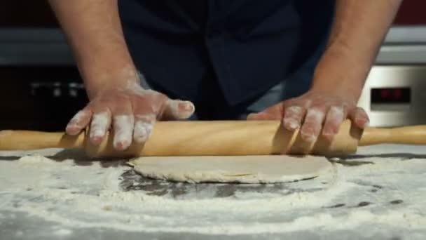 Férfi tekercs a tésztát egy sodrófa a konyhaasztalon.