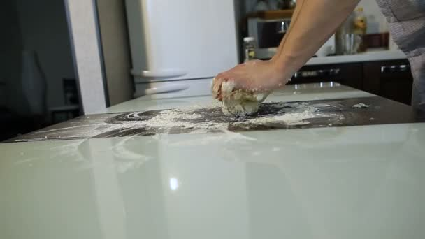 Mens hands prepare pizza dough on the table in the kitchen