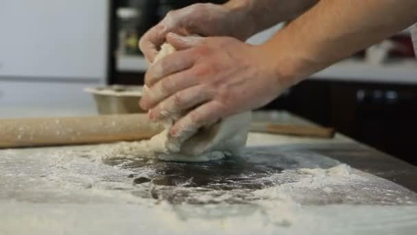 Männerhände bereiten Pizzateig auf dem Tisch in der Küche zu