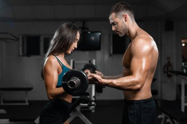 Man instructor and woman train in the gym, lifting dumbbells