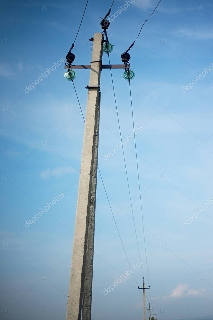 Electric poles of high voltage on blue cloudy sky background