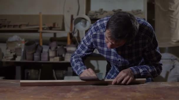 Carpenter polishes the wooden board with sandpaper on desktop. Work in the carpentry workshop
