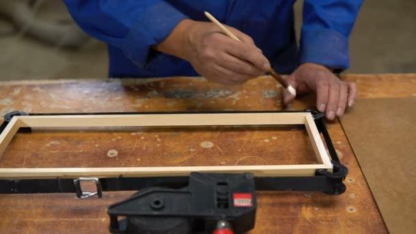 Montáž dřevěný rám na tabulce tesařství v dílně s lepidlem a různé nástroje