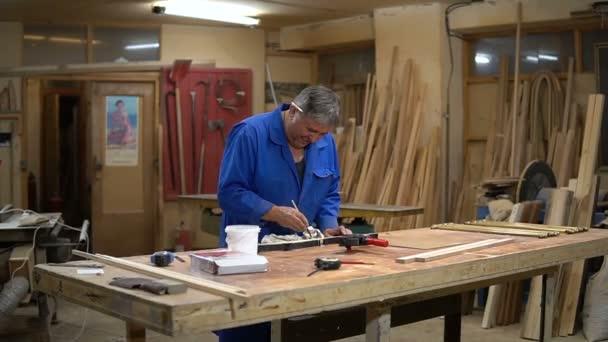 A fából készült keret összeállítása az Ács asztalon a műhelyben