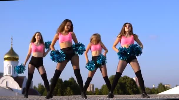 cheerleader girls with pompoms dance outdoors on sky backround