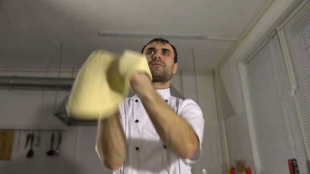 Koch in der Küche bereitet Pizzateig zu und jongliert mit den Händen