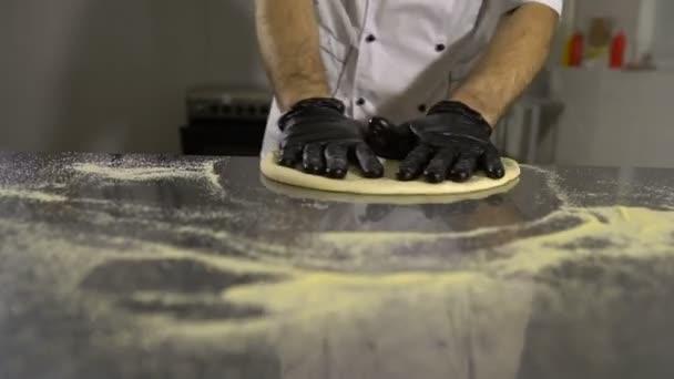 Koch in der Küche und bereitet Pizzateig zu. Mann bereitet Gebäck zu