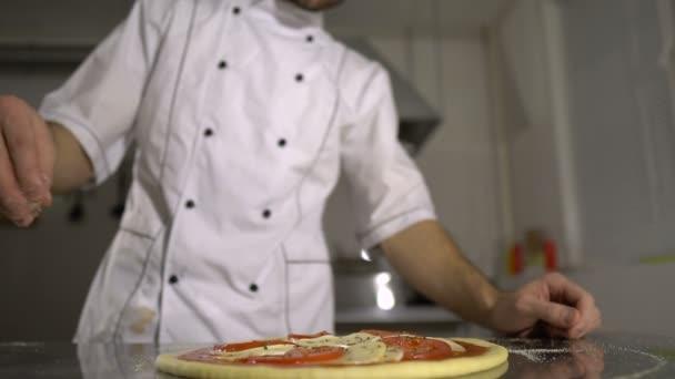 Kuchař posype kořením na hotové pizzy v kuchyni
