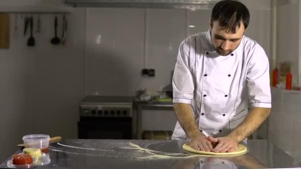 Vařit v kuchyni připravovat těsto na pizzu. Člověk připravuje pečivo