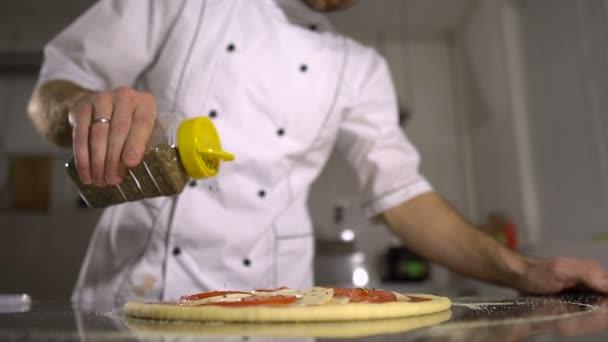 Szakács hinti fűszer a konyhában kész pizza