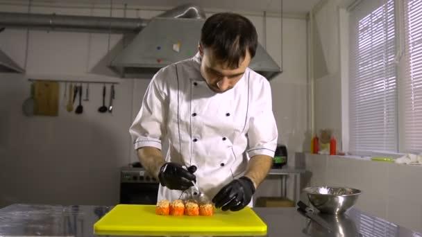 Šéfkuchař připraví japonských jídel, kuchař dělá sushi, připravuje sushi rolka, klade velmi chutné náplně