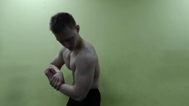 Atletický muž vystupují proti zdi v tělocvičně