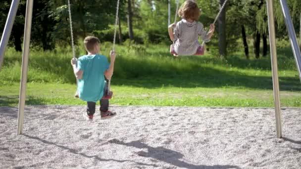 Bambini sulle altalene al campo da giuoco