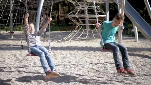 Děti na houpačkách na hřišti