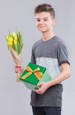 Holidays, Love, Happiness and People concept - Happy Child celebrating Valentines Day. Teen Boy with Flowers and Gift Box. Boy with bouquet of yellow tulips on gray background.