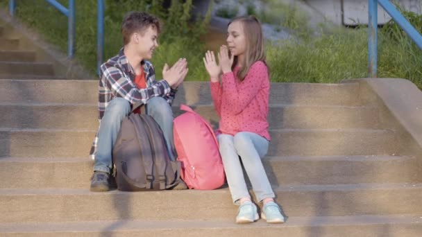 Mladík a dívka sedící na schodech