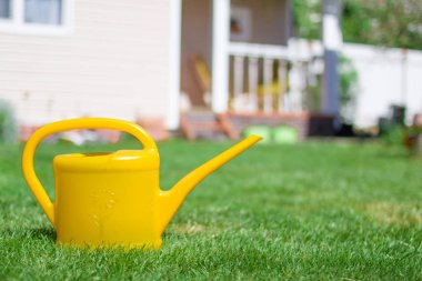 Yellow Watering can with house in background. Gardening or planting concept. Working in the garden.