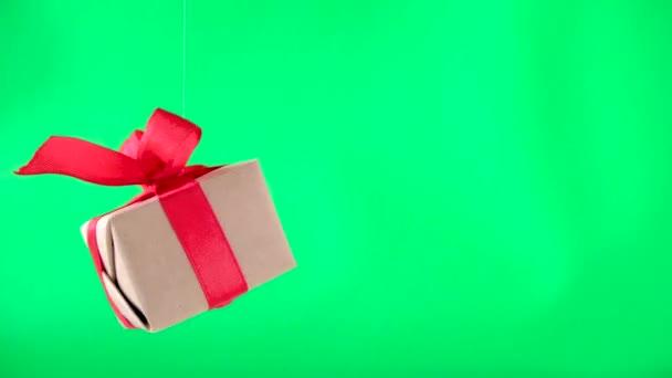 Díszdobozban piros szalag spinning a zöld képernyőn. 360 fok forgatás. varrat nélküli hurok. nulla gravitáció. Lebegés. chroma kulcs. Koncepció értékesítés, Akciós ár, karácsonyi ünnepek és vásárlás