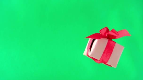 Dárkové pole s červenou stuhou, která se otáčí na zelené obrazovce. otáčení 360 stupňů. nepřerušenou smyčku. nulová gravitace. Levitace. Chroma klíčem. copyspace. Koncepce prodeje, Zlevněná cena, vánoční svátky a nákupy