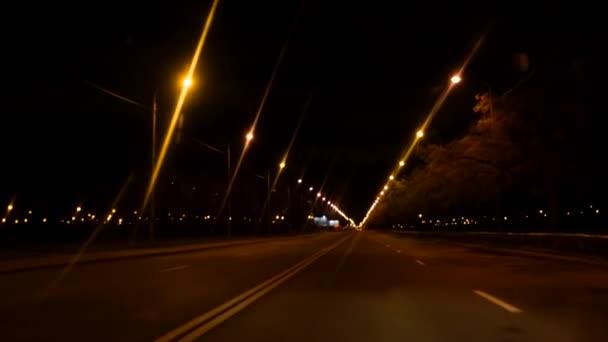 4k. Nachtfahrt auf leerer Stadtstraße aus dem Fenster des Speedcars, nach Regen verschwommenes Licht