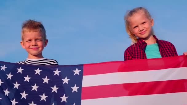 4k. Portrait of blonde boy and girl with national USA flag outdoors over blue sky on sunset at summer - american flag, country, patriotism, independence day 4th july.