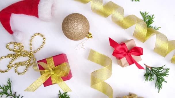 Otáčení vánočního pozadí. Dárkové krabice s červenou zlatou stuhou vánoční ozdoby, vánoční koule na bílém dřevě. Otočení o 360 stupňů. bezešvé smyčky. Koncepce prodeje, nakupování a oslavy