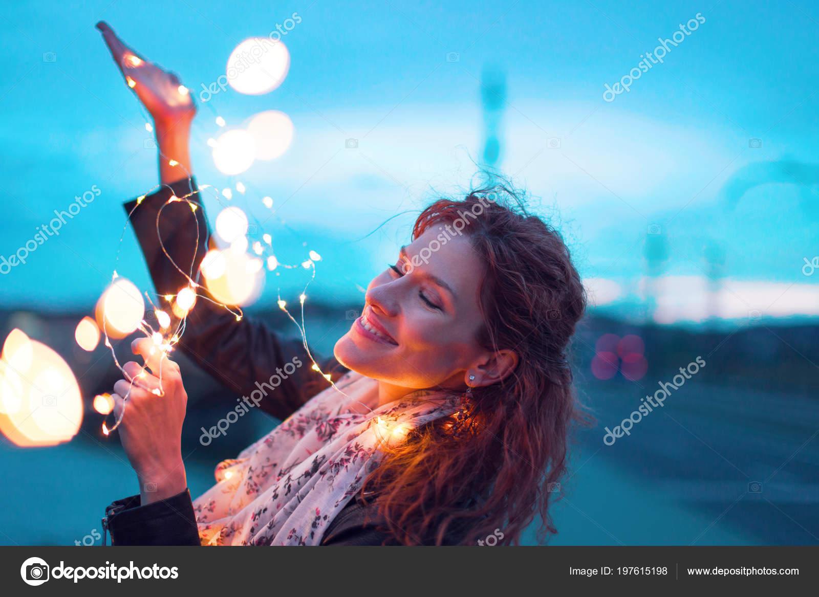 Gelukkige vrouw spelen met licht fairy garland avond buitenshuis
