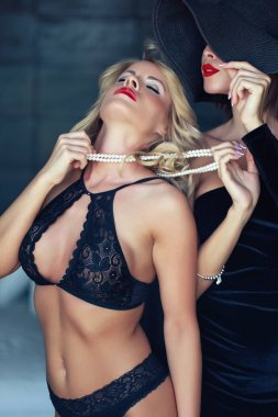Blonde woman in bra holded by lesbian lover on pearls sin