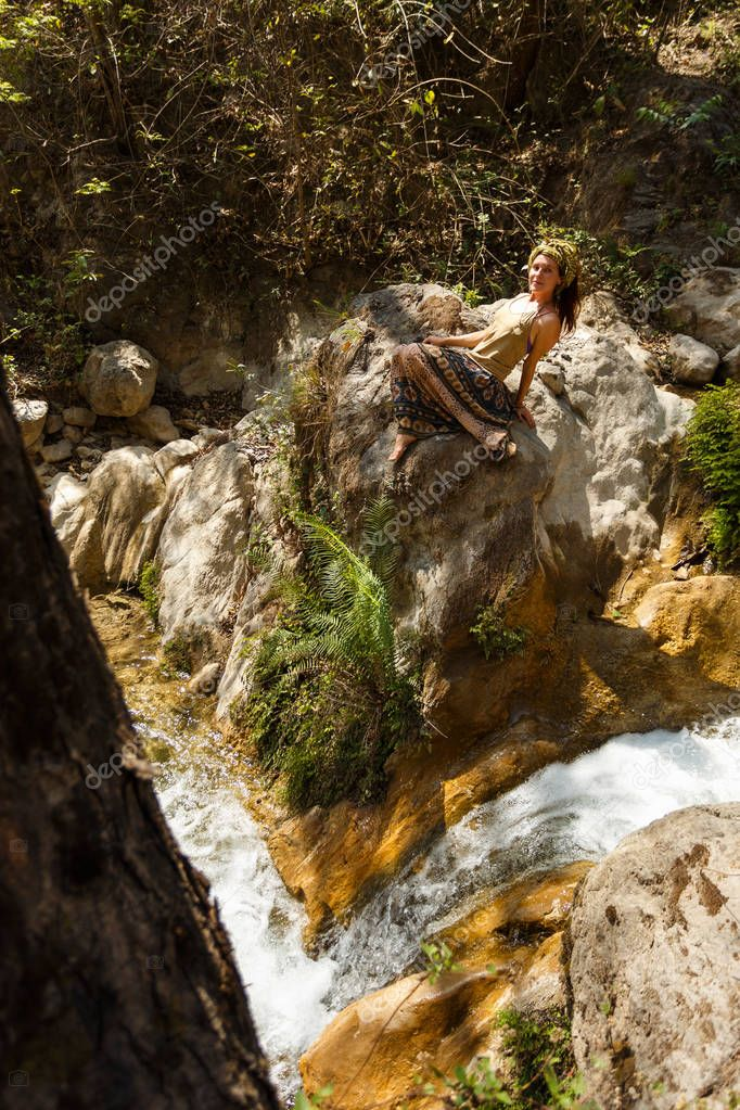 A woman lies on a stone next to a river in the forest and welcomes the sun.