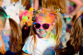 Portrét se dívky směje v slunečních brýlích v Holi Paint párty