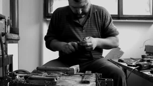 Řemeslník dělá postava s dráty ve své dílně. Umělec je zpracování kovu se speciální nástroji ve svých rukou křivku drátu do správného tvaru.