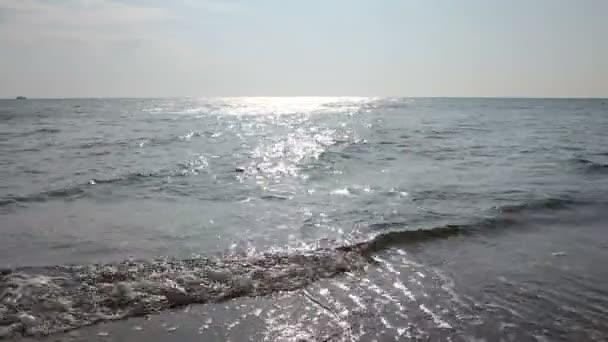 Moře rozbíjí vlny na písečné pláži, pobřeží. Nízký úhel pohledu na malé vlny na pobřeží, moře se zpěněné vlny. Videokodek Photo-JPEG