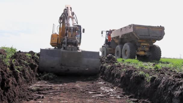 Big excavator is filling a dumper truck with soil at construction site, project in progress. H.264 video codec