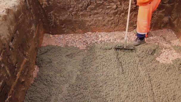 Pracovník po naliování betonuje beton. Mason používá hrábě k šíření čerstvého betonu v čtvercových zákopu. Videokodek H. 264