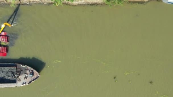 Letecký pohled na bagrovací bagr je bagrování, práce na řece, kanálu, prohloubení a odstranění usazenin, bahno z říčního dna ve znečištěné vodní cestě.