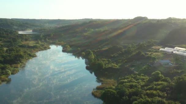 Langsam schießend über den See in der Morgendämmerung, am frühen Morgen, grüne Hügellandschaft, mehrere Gewächshäuser unter Waldbäumen.