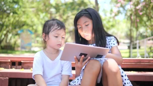 Šťastné děti hrají tabletu společně venkovní