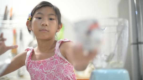 Asijská dívka dělat, odlévání, pití zelené zeleninové smoothie s mixérem. Zdravé stravování životní styl s mladou ženou, příprava prolnutí smoothie nápoj s kiwi doma v kuchyni