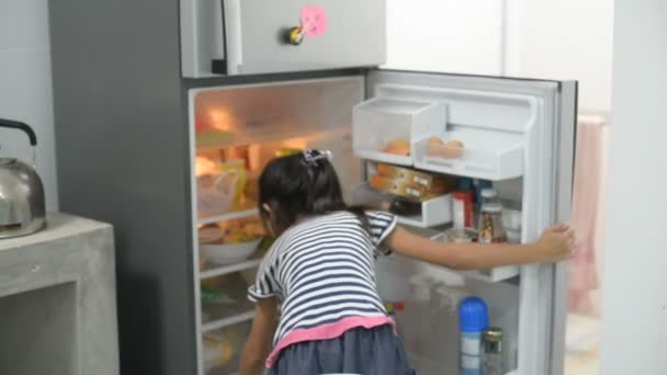 Asian girl open refrigerator and looking for something, take it and close the door.