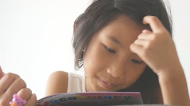 Asijská dívka ležela na pohovce číst knihu a usmívá se