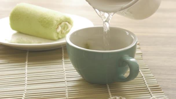 Tè verde che versa nella tazza asiatica con sfondo torta rotolo