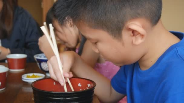 Asian kids eating Japanese food sushi in a restaurant, Sushi is a traditional food of Japan
