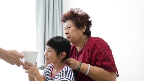 Asijská dívka pití šálku vody, zatímco její babička pletení vlasy.