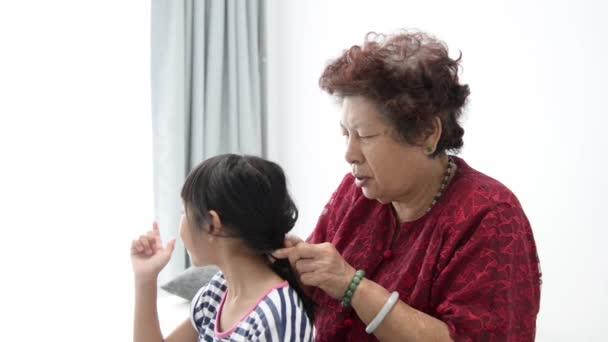 Asijské starší ženy prýmky její vnučka vlasy, rodinné životní styl doma.