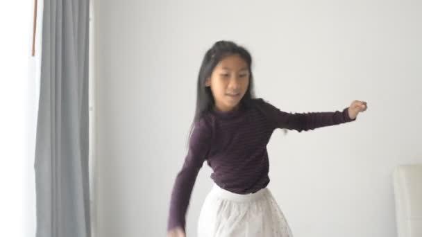 asiatische Mädchen spielen einen Hula-Hoop-Reifen in der Nähe von Fenster zu Hause
