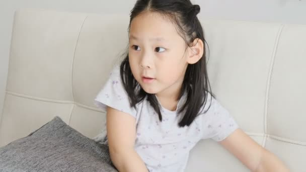 Happy Asian girl sitting at sofa and trying to talk with microphone at home.