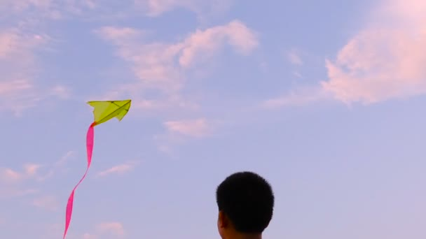 Young boy playing with kite on the beach during sun set, slow motion.